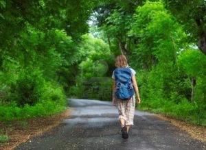 11540774-femme-avec-sac-a-dos-marche-sur-une-route-mouillee-entre-les-verts-des-arbres-tropicaux